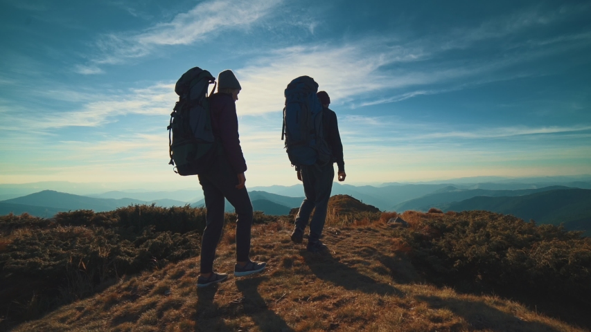 The couple walking on a mountain against a bright sun. slow motion   Shutterstock HD Video #1030416137