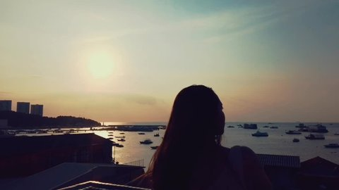 PATTAYA, THAILAND - MAY 1, 2019 : Attractive happy woman looking see view sunset at Pattaya seascape from of the roof top on vacation. With noise blurry background.