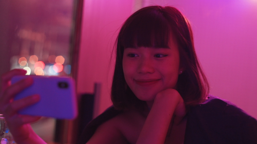 Young asian millennial woman taking selfie at nightclub bar, neon pink background | Shutterstock HD Video #1030455557