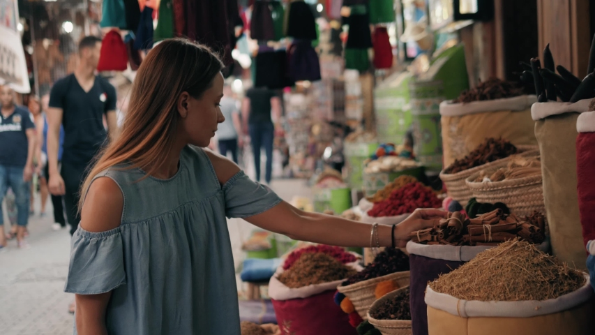 Woman walking on MAROCCAN MARRAKECH spices market. Woman walking on beautiful african arabian spices market and choose spices, travel tourist | Shutterstock HD Video #1030470437
