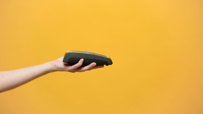 Close up cropped photo of female holding in hands wireless modern bank payment terminal to process acquire credit card payments black card isolated on yellow background. Copy space mock up advertising