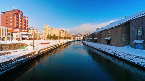 Daytime beauty after a winter snowfall of the Otaru Canal in Hokkaido, Japan, a popular skiing destination. Traffic passing on a street and wind blowing across the surface of calm water.