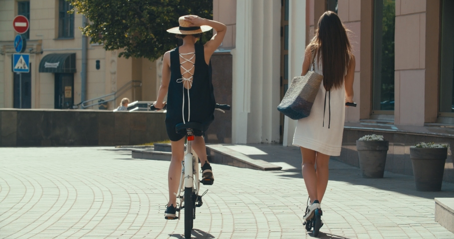 Two women walking together on street. Lifestyle and health in city. Girls riding vintage bike and electric scooter on urban background. 4K slow motion video footage 60 fps | Shutterstock HD Video #1030533017