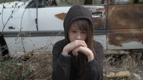 Child loneliness. Sad girl orphan thought. Homeless child is depressed.