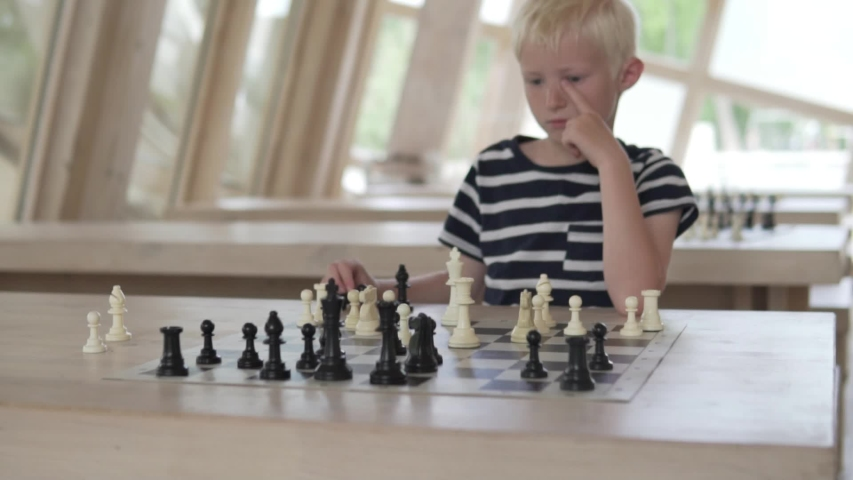 The boy plays chess. The child sits in a spacious bright chess club and waits for the opponent's turn. | Shutterstock HD Video #1030593107