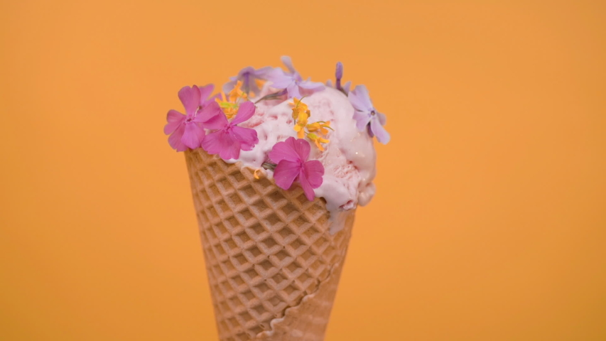 Ice cream scoop in waffle cone decorated with spring flowers, vanilla style | Shutterstock HD Video #1030613537