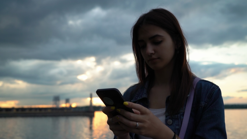Lonely and calm caucasian girl standing on the quay with smartphone in hands and surfing in social nets | Shutterstock HD Video #1030676237