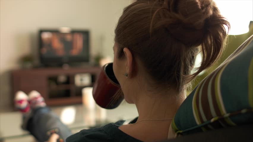 Rear view of young caucasian woman laying on couch with colorful socks. She puts her feet on table and relaxes. The girl watches TV and holds remote control