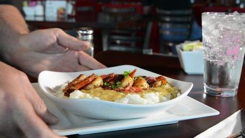 Waiter serving a Cajun shrimp dish in a restaurant