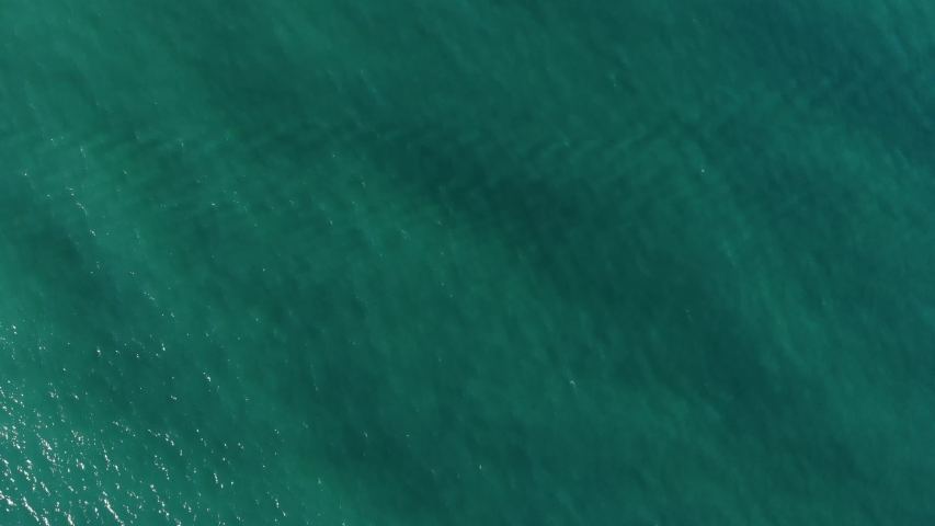 Aerial top down view from high altitude of green sea water texture. The camera flies over the water, a view of the water surface. Background of the water surface. 4K aerial view | Shutterstock HD Video #1030731017