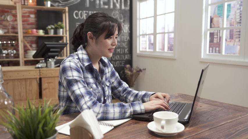 Beautiful asian chinese woman freelance enjoying coffee cappuccino with foam in cafe bar. female sitting in shop drinking chocolate smiling looking window daydreaming while typing working on laptop | Shutterstock HD Video #1030777487