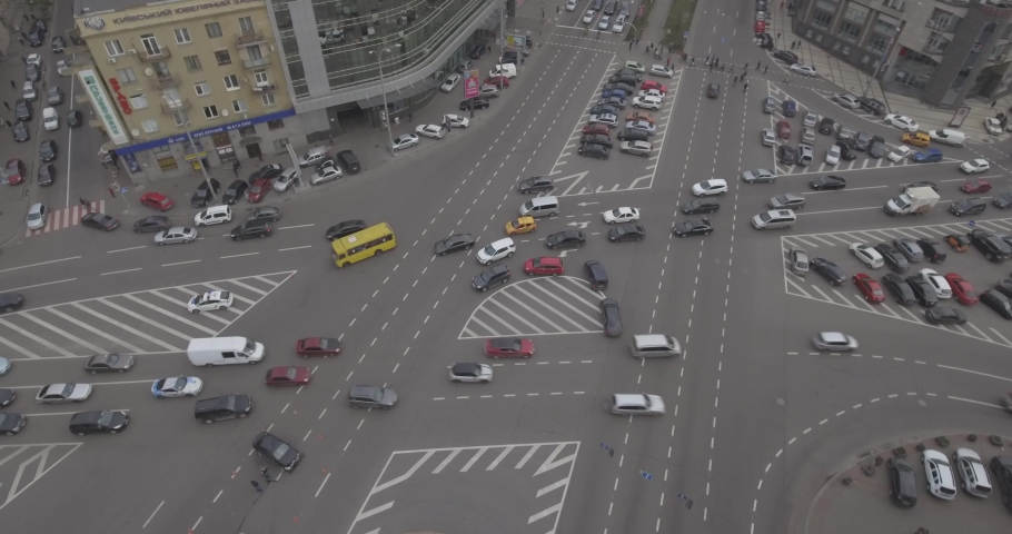 Aerial view of the road intersection, traffic at rush hour with cars on the road. Victory Square in the city of Kiev overloaded with public transport. 19. May. 2019. Filmed from 4K drone in RAW. Video | Shutterstock HD Video #1030864007
