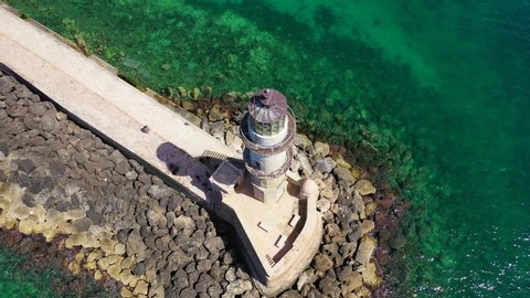 Aerial drone video of iconic Venetian lighthouse in the entrance of picturesque old port of Chaniawith beautiful colours, Crete island, Greece