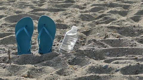 Mans hand is taking bottle with water near flip flops on beach