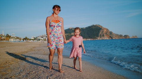 Mother wearing colorful dress with her happy daughter holding hands walking on beach along coastline. Clear blue sky, mountains and sea waves in background. 4k, slow motion.