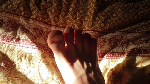 Feet on the bed. Bare feet on the blanket.