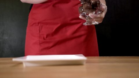 Macadamia nuts on plate. Action. Close-up of woman in apron puts three macadamia nuts on sample on black isolated background