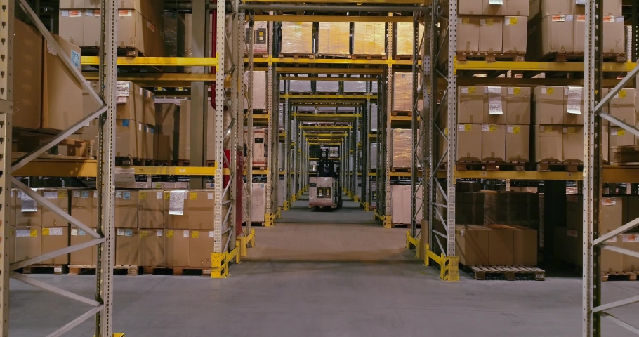The forklift carries boxes with products at the warehouse, forklifts traveling between the rows in the warehouse. Industrial interior | Shutterstock HD Video #1031184227