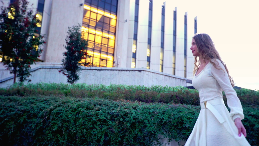 Girl with long blond hair runs on evening street outdoor. Young woman in white dress is in hurry to date in night city.