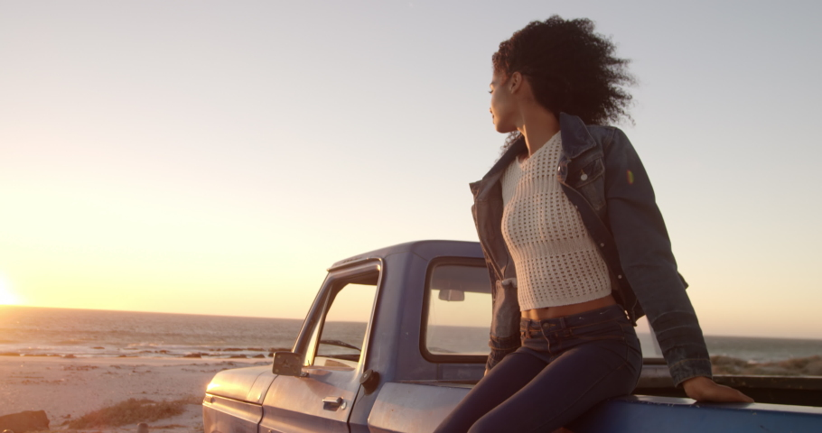 Front view close up of African american woman sitting on trunk of pickup truck at beach. She is looking away