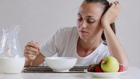 Portrait of tired young woman in white t-shirt mixes cornflakes with milk in a bowl. She doesn't want to eat them and lies on the table.