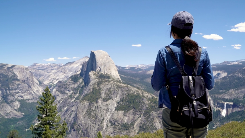 Back view of japanese lady tourist on peak of high rocks in yosemite national park sightseeing half dome trail view with blue sky. Sport active life concept. relax woman backpacker on mountain top | Shutterstock HD Video #1031281277