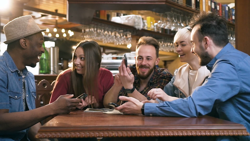 Company of focused hipster friends using smart phone in the bar, pub while caucasian man start celebrating win in the lottery and showing smart phone to the friends. | Shutterstock HD Video #1031304767