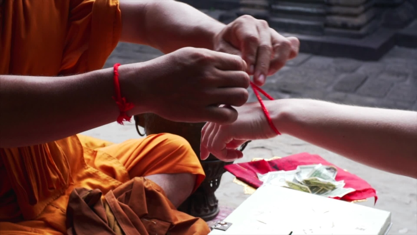 Unidentified monk is tieing the red thread around woman's wrist as blessing for luck and peace. Religious ritual in Angkor Wat temple, Cambodia #1031304977