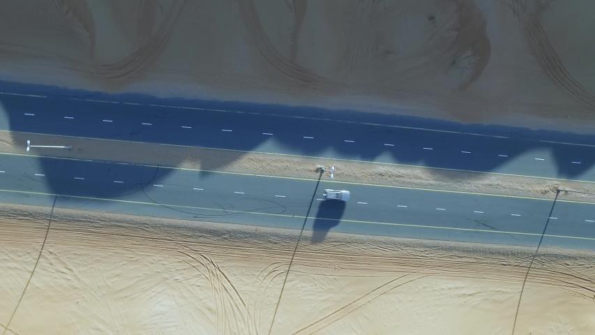 Aerial Drone bird's eye view top shot of card driving along a desert highway #1031405477
