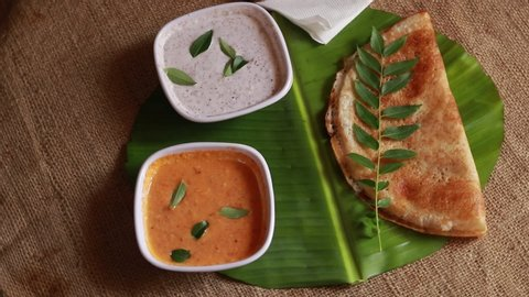 Rotating masala dosa / indian savory crepes with potato filling , top down  view