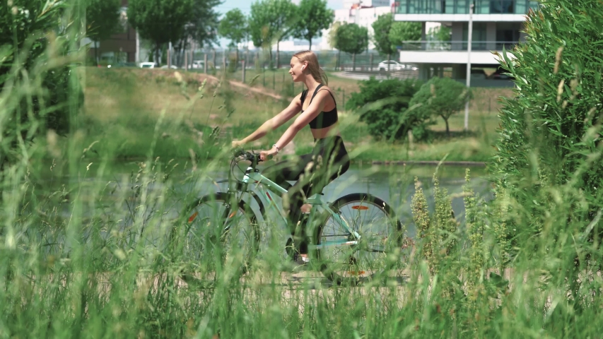 Young girl ride a bike in a city nature park, view through the grass near the river, calm mood. | Shutterstock HD Video #1031490737