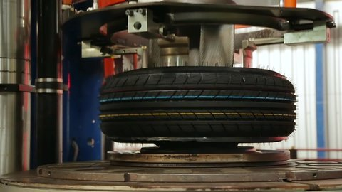 Car tires automatic building machine in process of tire forming. Car tire vulcanization shop. Tyre production machine. Vulcanization of tires at high pressure and temperature.