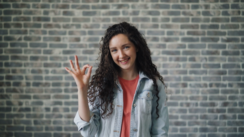 Portrait of glad young lady showing OK hand gesture smiling looking at camera standing against brick wall background. Millennials and evaluation concept. | Shutterstock HD Video #1031587367