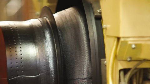 Tire production machine close up. Car tires automatic building machine in process of tire forming. Tire manufacture robotic equipment on tyre building plant at works. Robotic machine in a tire factory