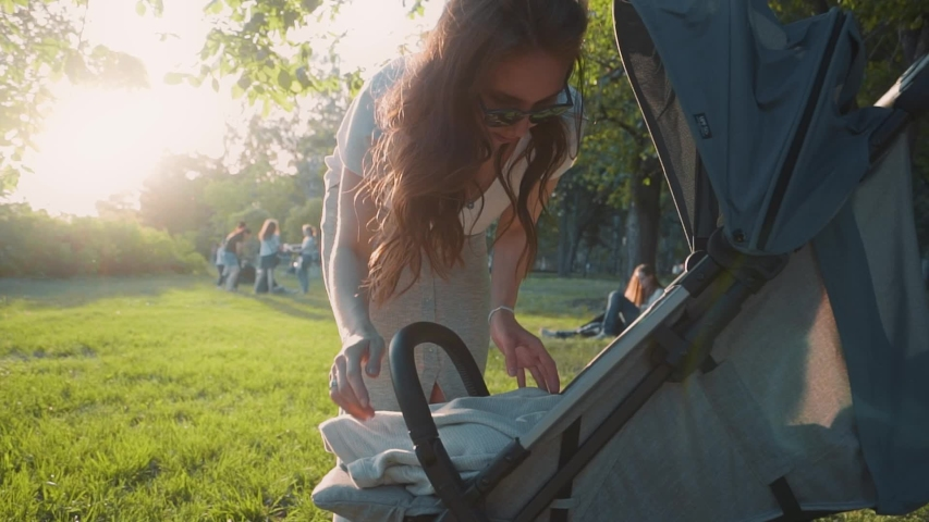 A beautiful young mother on a summer day covers a newborn baby with a blanket in a baby carriage in the Park, at sunset, outdoors. Family ties, sleeping on the street, summer. Slow motion #1031622287