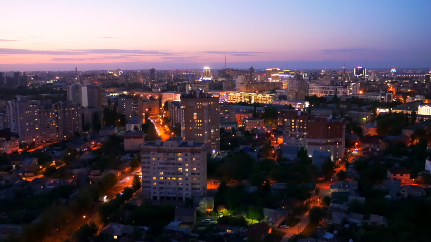Evening cityscape after sunset. Modern city with buildings, roads and car traffic in twilight, view from rooftop. | Shutterstock HD Video #1031638577