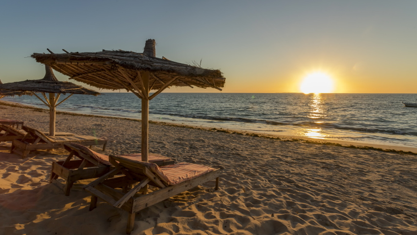 Anakao beach, Tulear, Madagascar. Time lapse  Wooden reclining lounge chairs  with thatched roof umbrellas on a sandy beach with sunset over the ocean.  | Shutterstock HD Video #1031680577