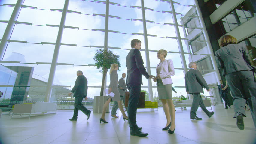 4K Businessman and businesswoman meet and shake hands in busy modern office building | Shutterstock HD Video #10316930