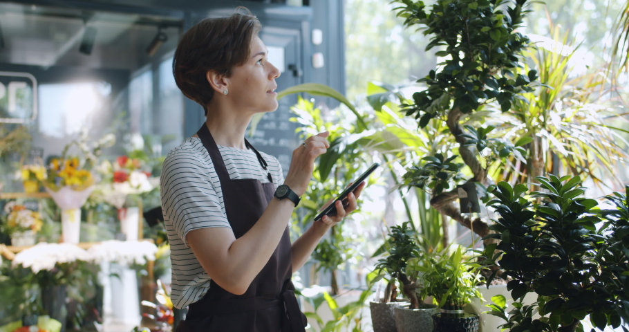 Young entrepreneur touching tablet screen looking at flowers in florist's shop enjoying nature and modern technology. People, entrepreneurship and business concept. | Shutterstock HD Video #1031741117