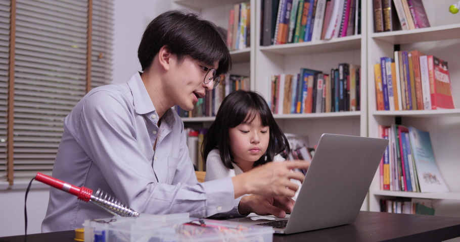 Teacher training little girl to learn haow to coding at home. Technology and Education concept. | Shutterstock HD Video #1031814197