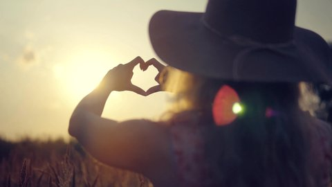 Woman In Hat Enjoing Sun.Girl Made A Heart From Hands.Woman Making Heart Shape With Hands.Love Sign Made With Fingers.Glare Of Summer Sun On Hands.Sun Rays Glide Arms And Hands.Attractive Woman Relax