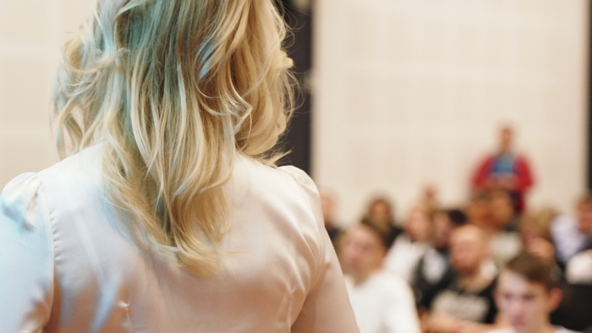 Female financial coach emotional speaking with spectators at forum. Person standing on the stage in front of rows of seats. Person on the public. Backview.   Shutterstock HD Video #1031877047