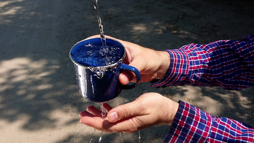 Crystal clean water puring to metal cup in hand slow motion. Dry sand in the background. Humanitarian crisis, global warming and thirst quench concept. | Shutterstock HD Video #1031916977