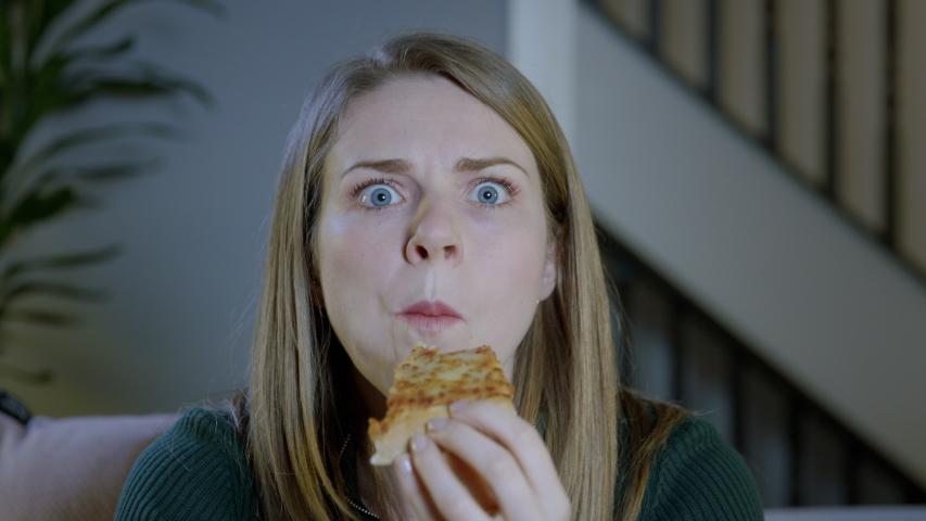 Young woman eating a takeaway pizza slice at home while watching TV | Shutterstock HD Video #1031984357