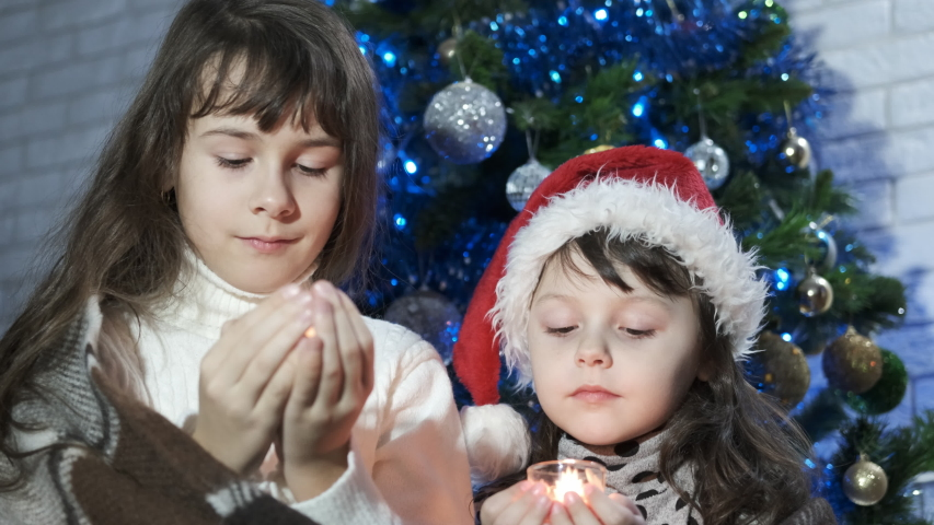 Flame of the candlestick. Warmth of family relations. Girls stay with candlesticks near a Christmas tree and look at the trembling candle flame.   Shutterstock HD Video #1032010937