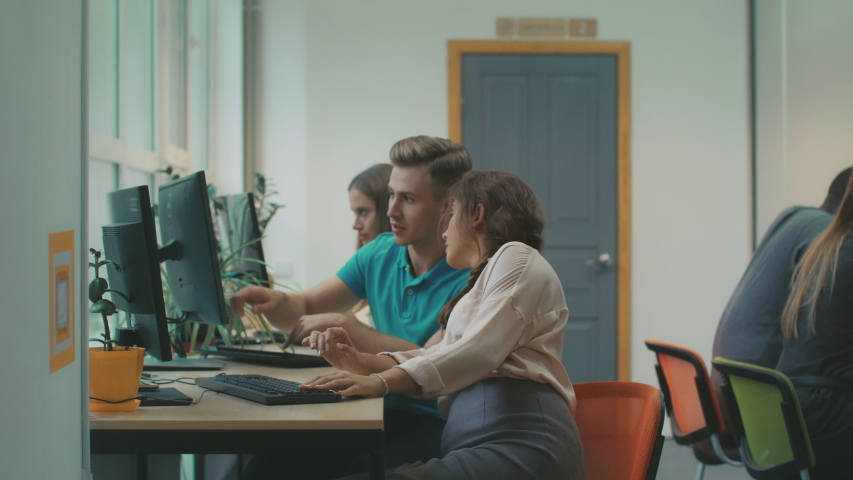 Young woman consulting with colleague about working question. Pretty lady looking in computer at coworking. Smart guy explaining project details in office. | Shutterstock HD Video #1032162857