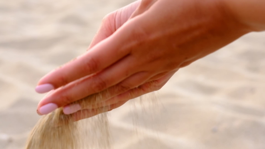 SLOW MOTION, CLOSE UP: Unknown playful young woman throws a handful of white sand. Time is running like the sand through your fingers. The sand pours through the fingers of the combined palms | Shutterstock HD Video #1032204527