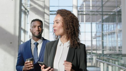 mixed race business woman chatting to african american businessman female executive using smartphone discussing work sharing ideas walking in office lobby
