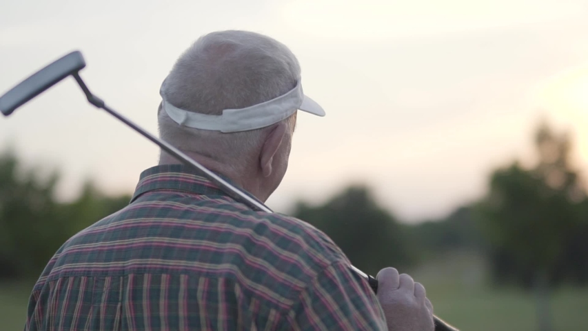 Back view of mature man playing golf on the golf course. Senior man looking away with the club on his shoulder. Old gentleman playing game outdoors. The concept of recreation and sports outdoors. | Shutterstock HD Video #1032487427