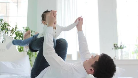 dad and his cute and lovely daughter playing joyfully in a bright room